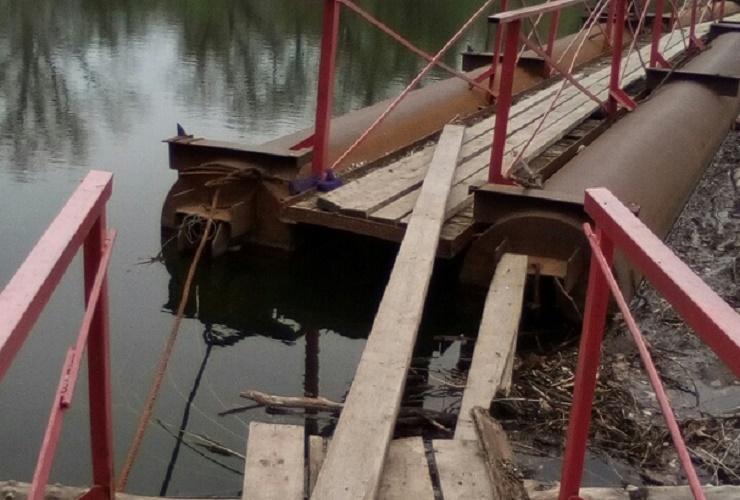 Балаковские пенсионеры переходят реку по опасному мосту
